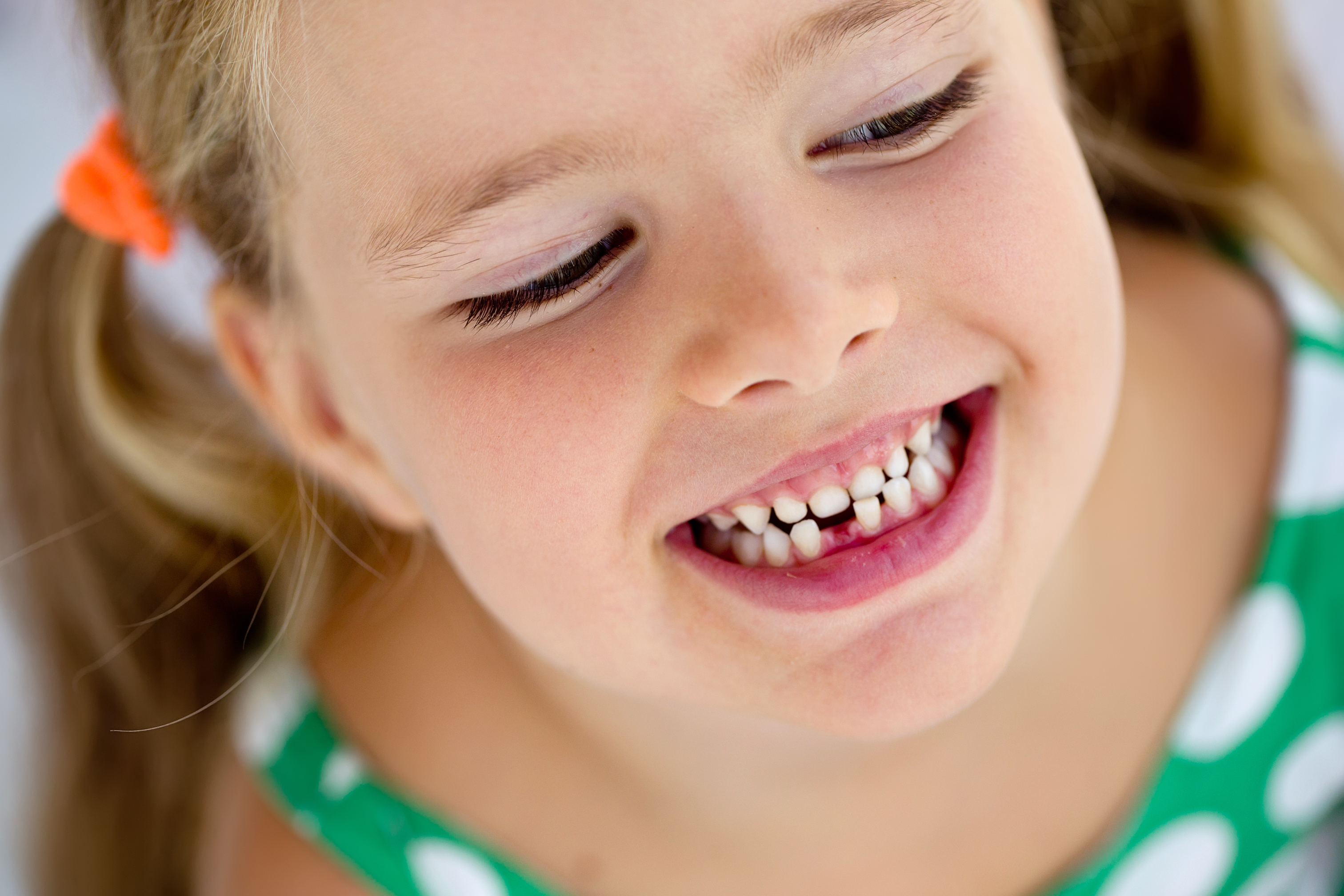Young girl smiling with missing tooth