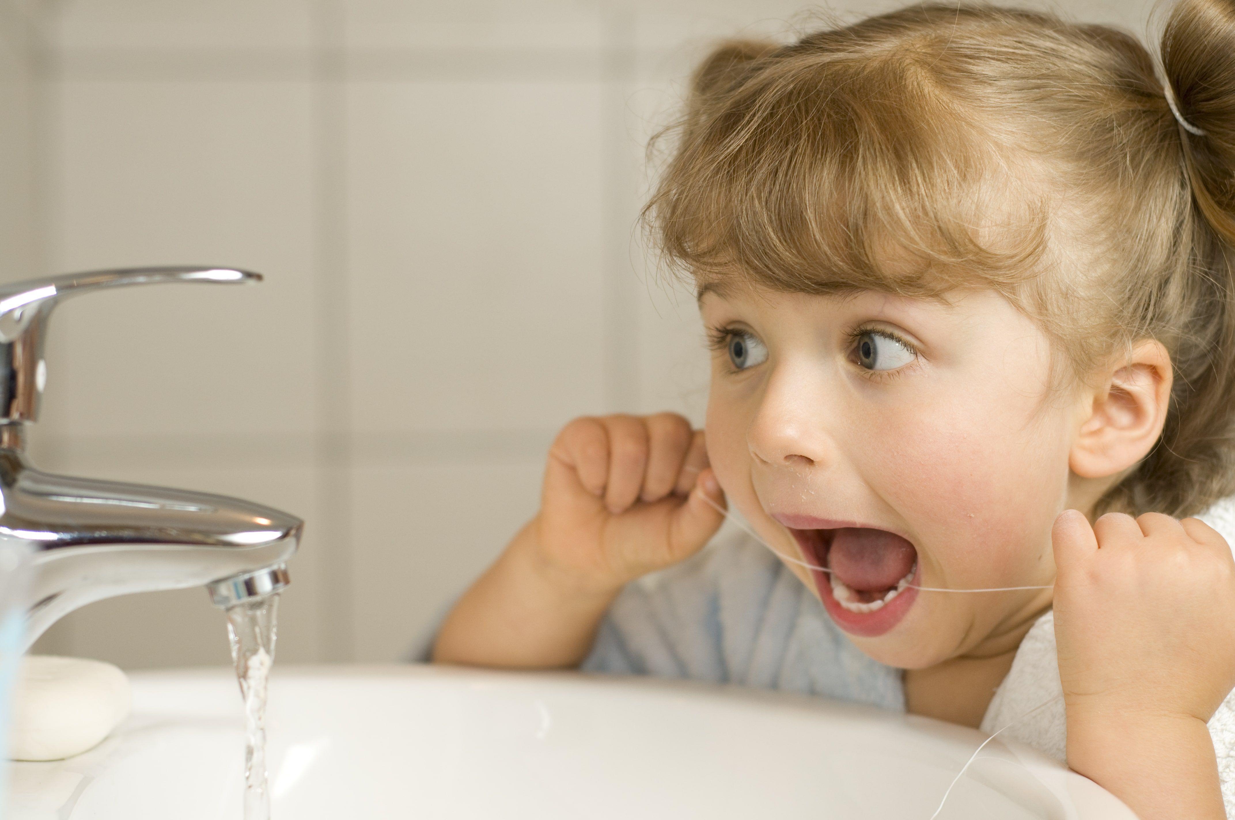 Cute girl cleaning teeth by floss in bathroom