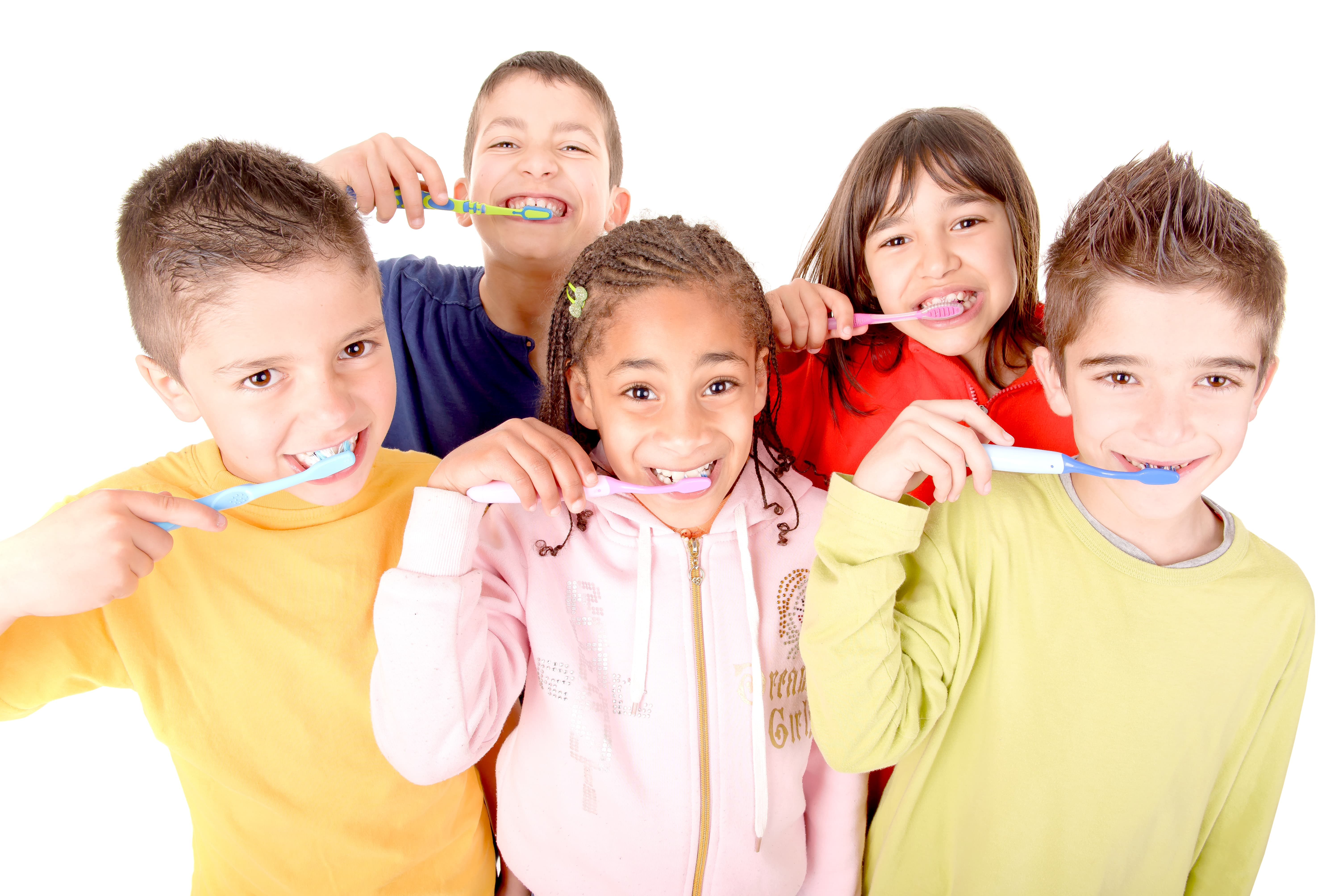 A group of five kids brushing their teeth