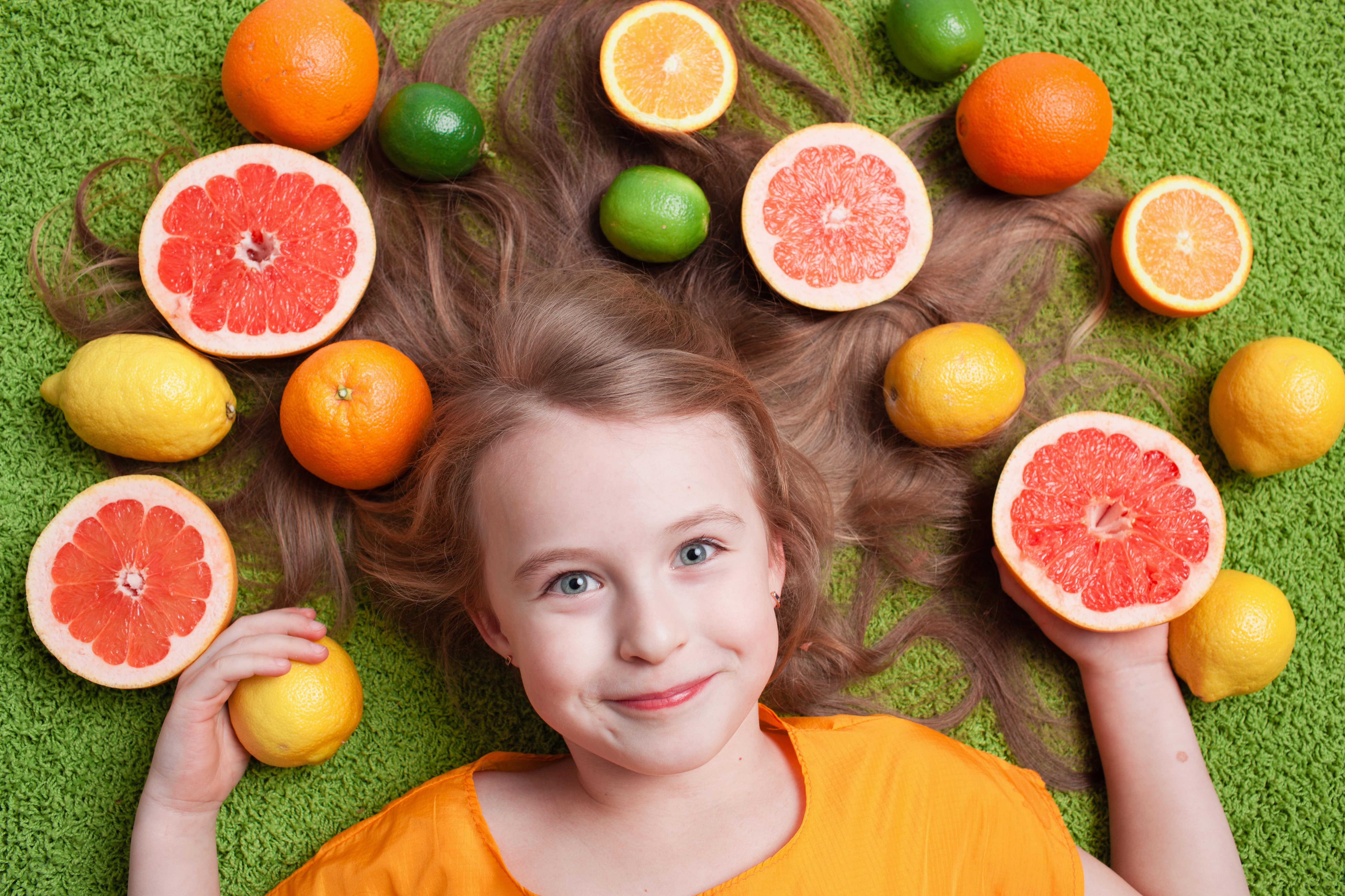 Blonde girl laying down on a green background with her hair spread out and surrounded by citrus fruits